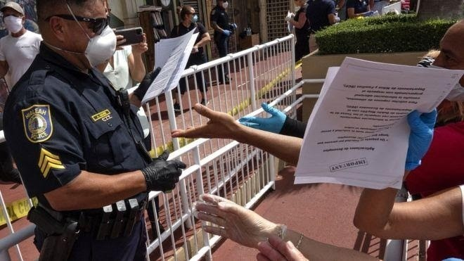 A police officer hands out unemployment benefit applications in a car park in Florida
