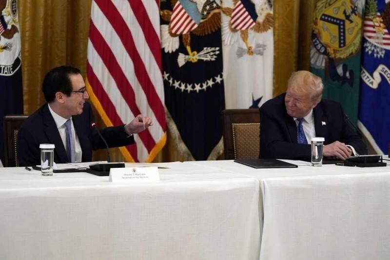 President Donald Trump smiles as Treasury Secretary Steven Mnuchin hands him a debit card that will be used to send payments by the Treasury Department to Americans during a Cabinet Meeting in the East Room of the White House, Tuesday, May 19, 2020, in Washington. (AP Photo/Evan Vucci)