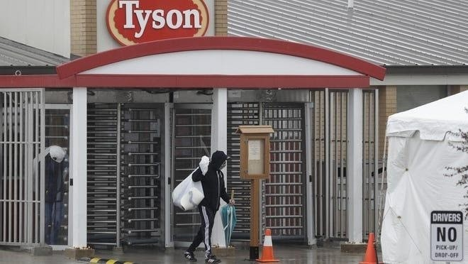 An employee leaves the Tyson Fresh Meats plant in Logansport, Ind. The plant will temporarily close its meatpacking plant in north-central Indiana after several employees tested positive for COVID-19.