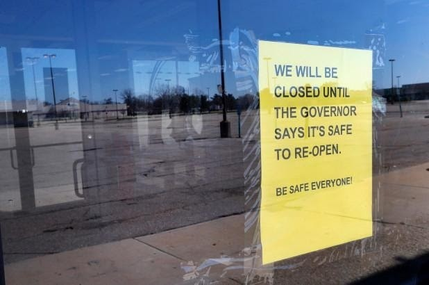 A closed sign is shown at Romeo and Juliet Furniture and Appliances with an empty parking lot in Detroit.